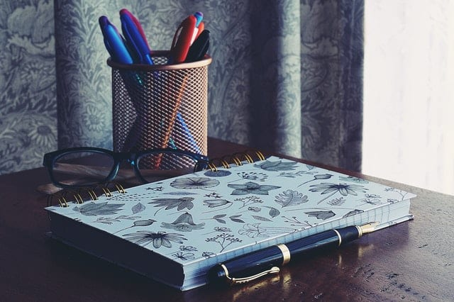 Photography of notebook near pens
