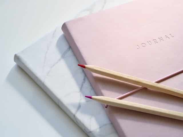 Closeup photo of journal books and pencils